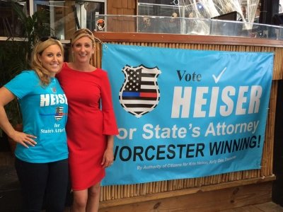 Kris Heiser standing with a support of her campaign in blue t-shirts