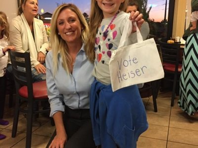 Kris Heiser stands with girl supporting her campaign in their blue t-shirts